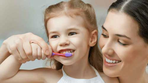 mom-and-daughter-brushing-teeth-min